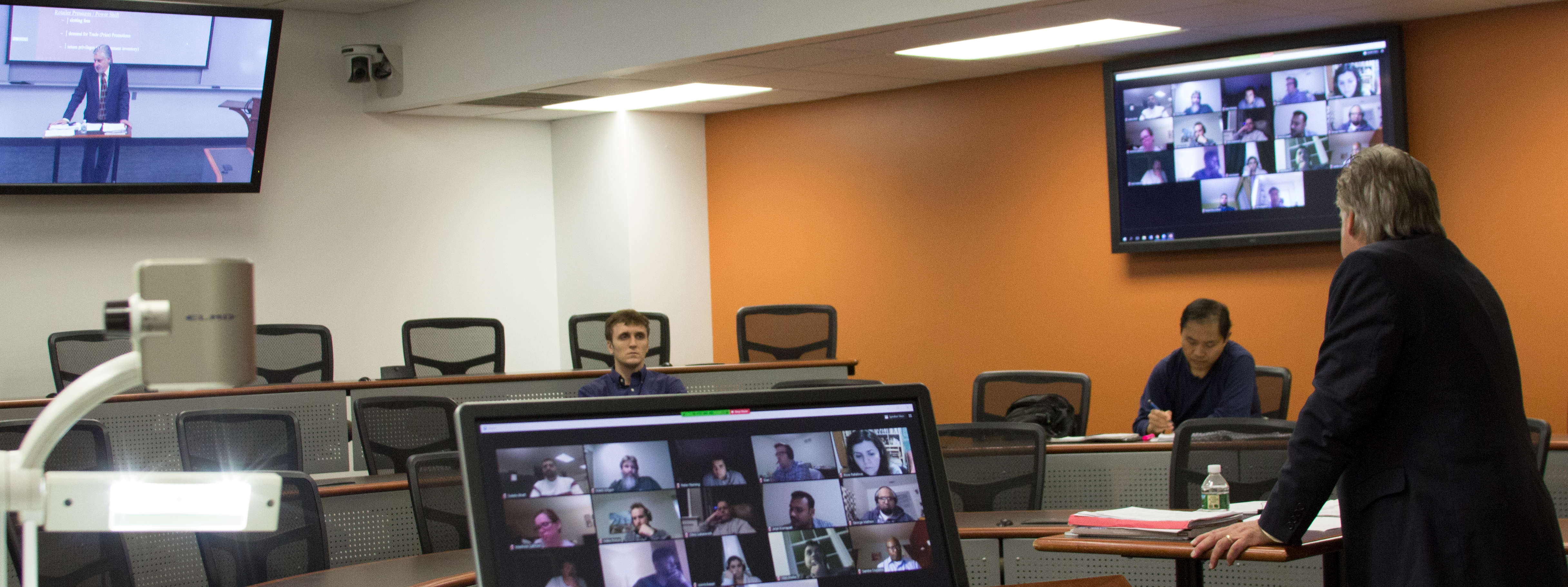 Instructor and students in the room viewing video feeds from students online